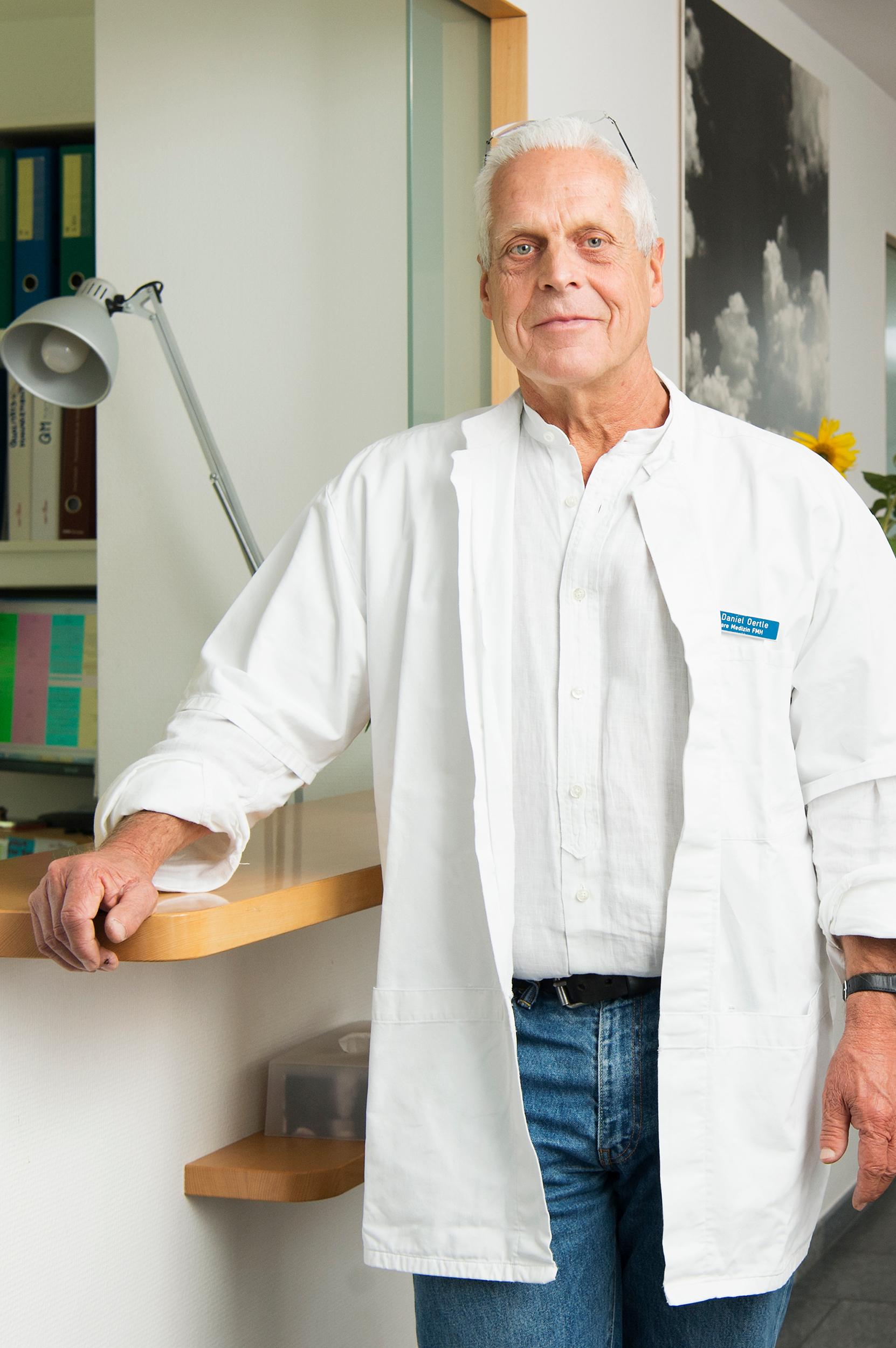 Portrait von Dr. Daniel Oertle, stehend vor dem Empfang der Praxis.