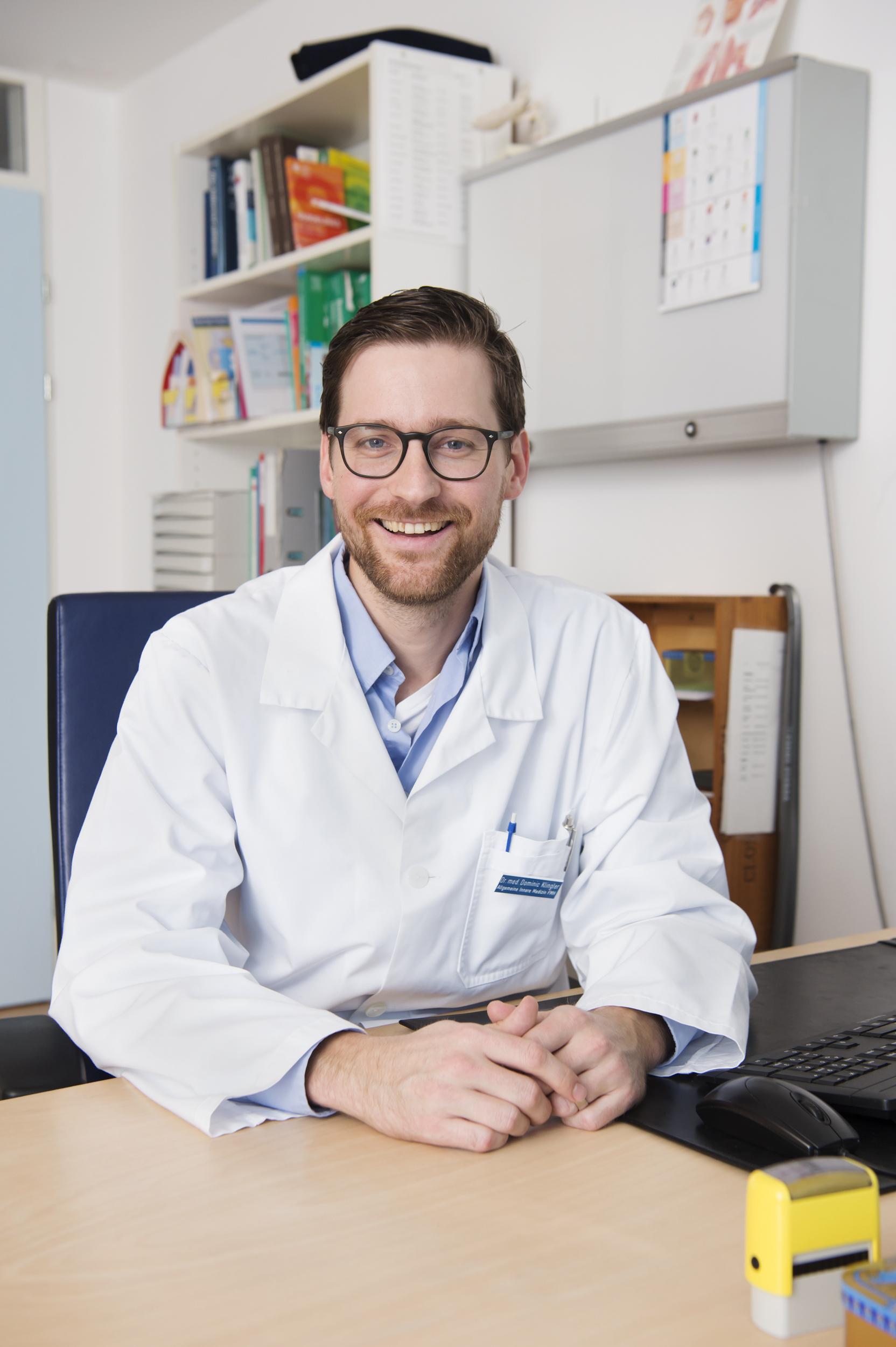 Portrait von Dr. Dominic Klingler an seinem Schreibtisch in seinem Sprechzimmer.