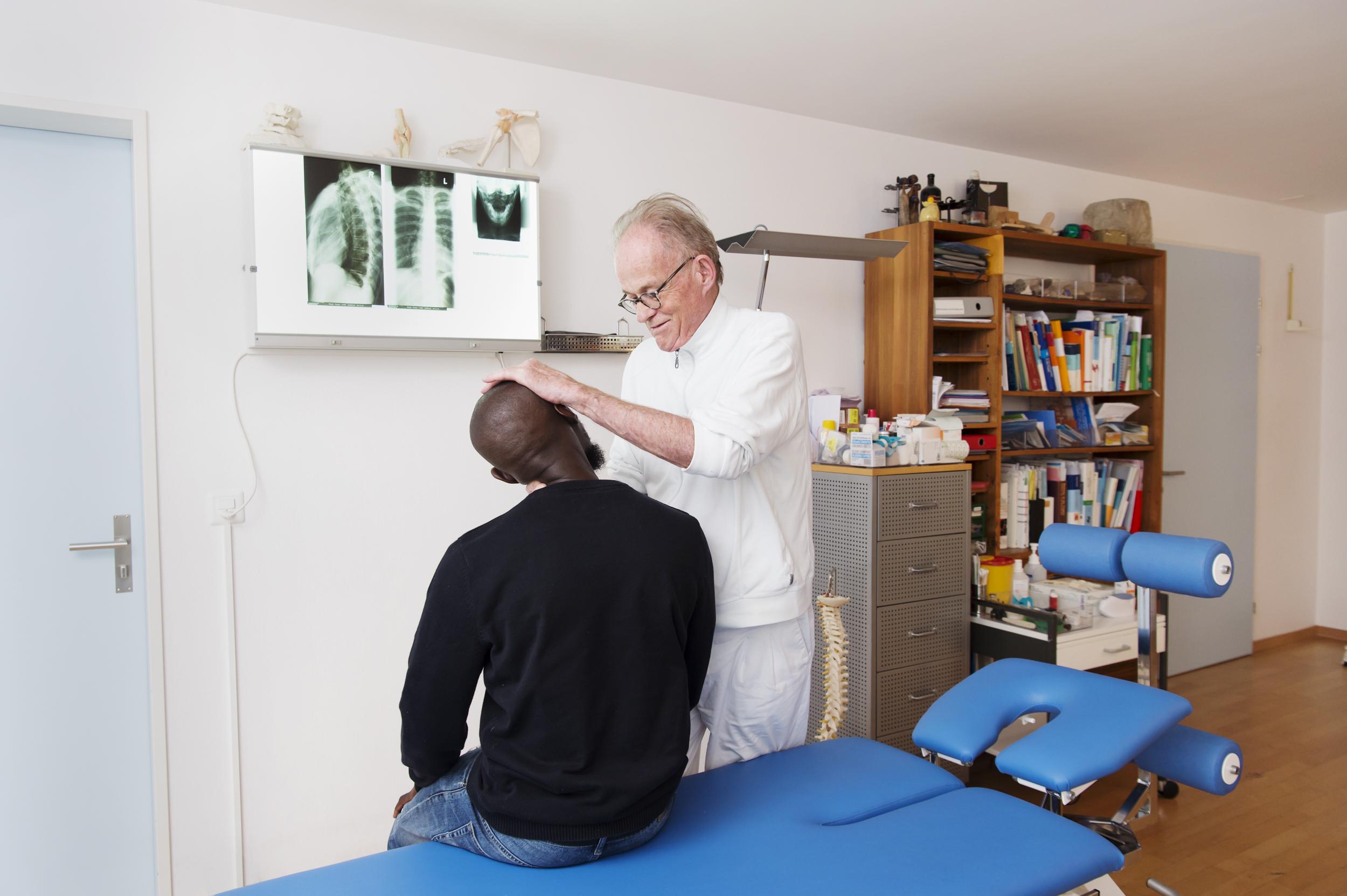 Dr. Maggi behandelt einen Mann am Nacken.
