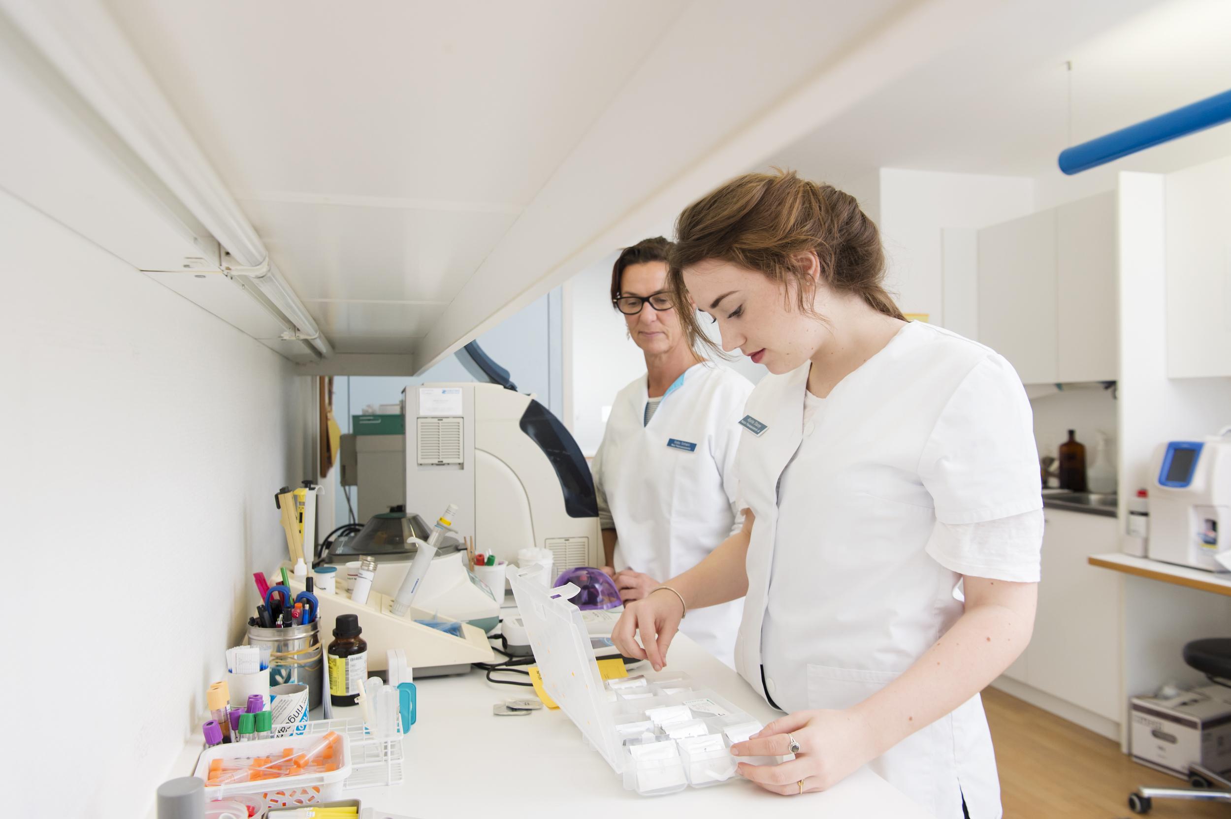 Zwei medizinische Praxisassistentinnen bei ihrer Arbeit im Labor.