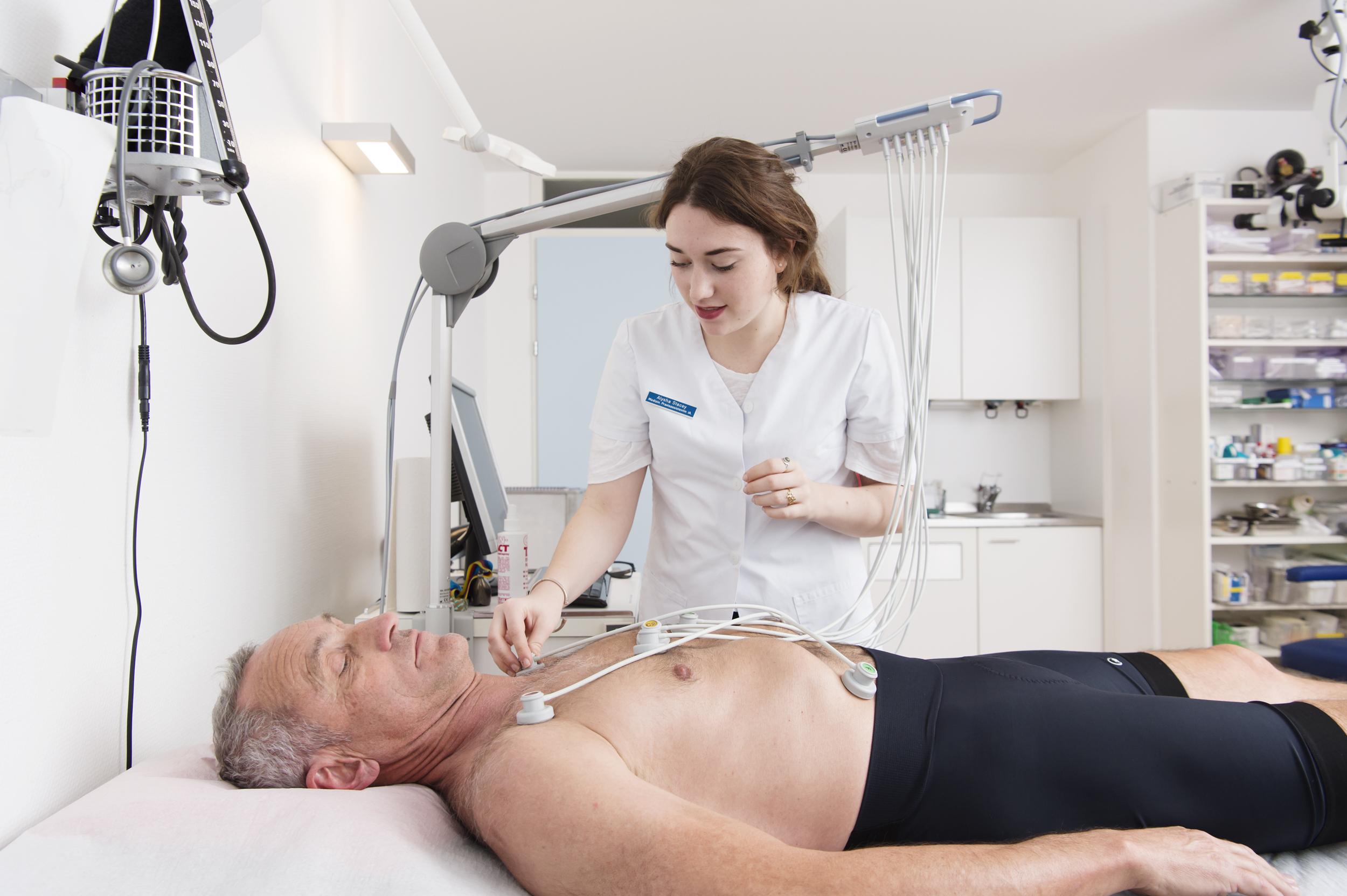 Eine MPA bei aufsetzen eines EKGs bei einem Patienten.