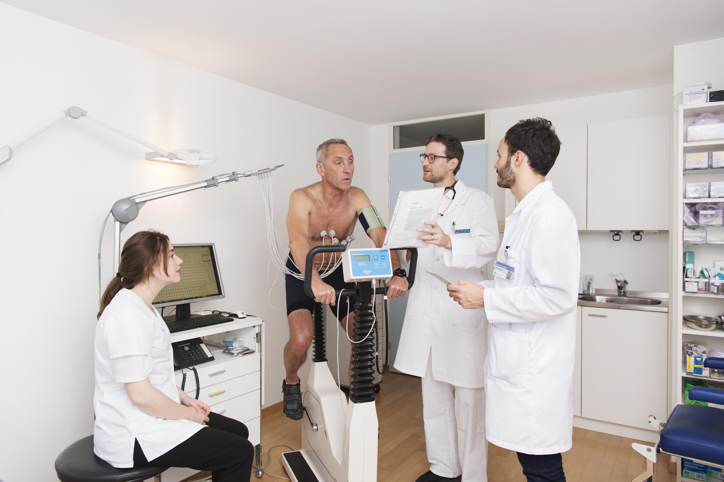 Dr. Klinger mit einem Assistenzarzt und MPA an besprechen mit dem Patienten den Ergometrie Ablauf.