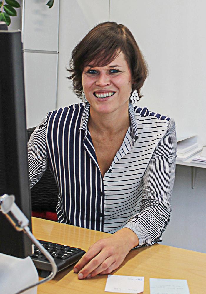 Portrait von Dr. Corinne Gmünder an ihrem Schreibtisch in ihrem Sprechzimmer.
