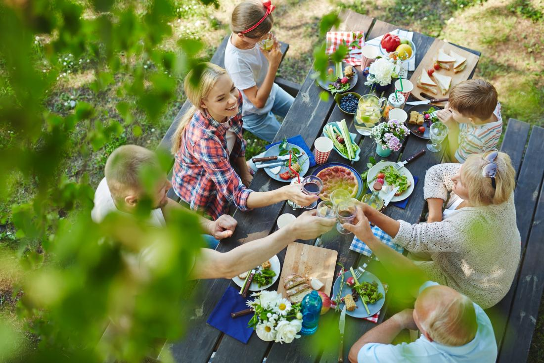 Picnic on table with lots of food outdoors.
