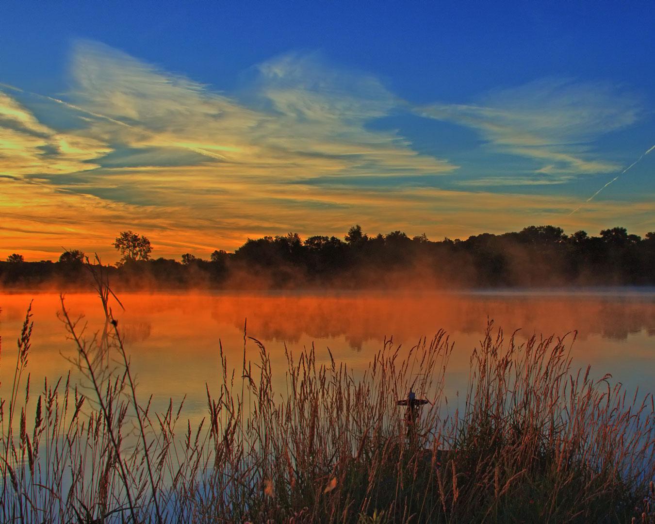 misty red sunrise over a large pond