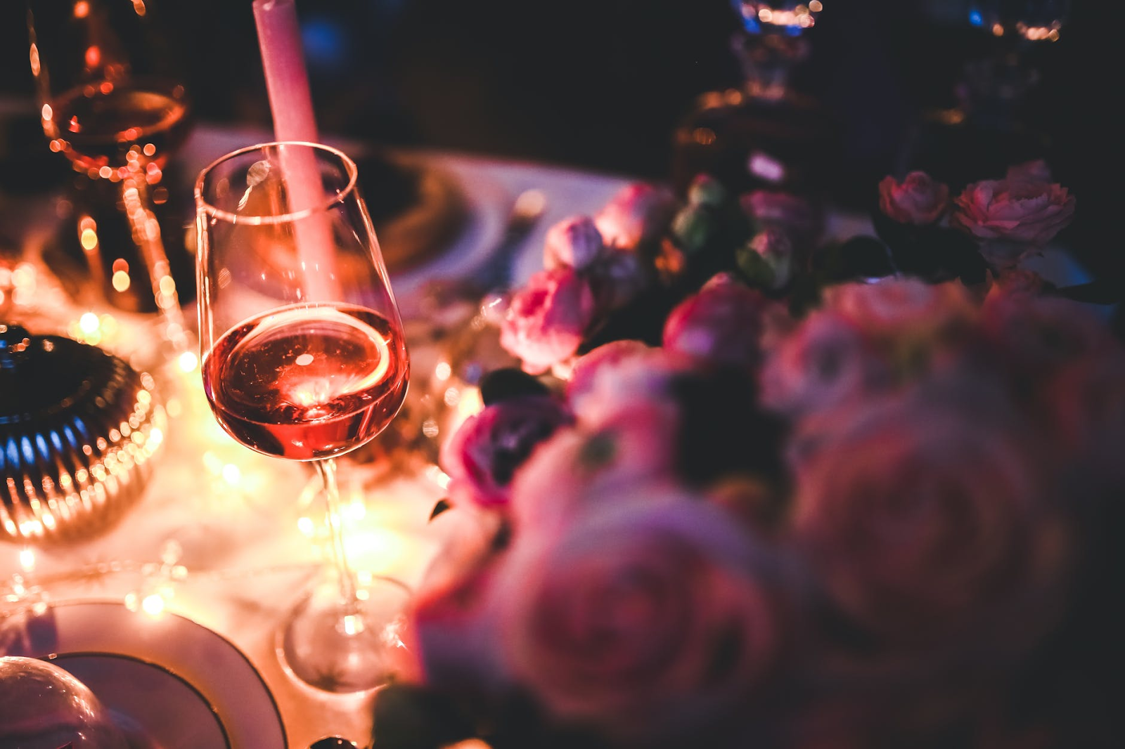 close-up of wine glass next to pink roses