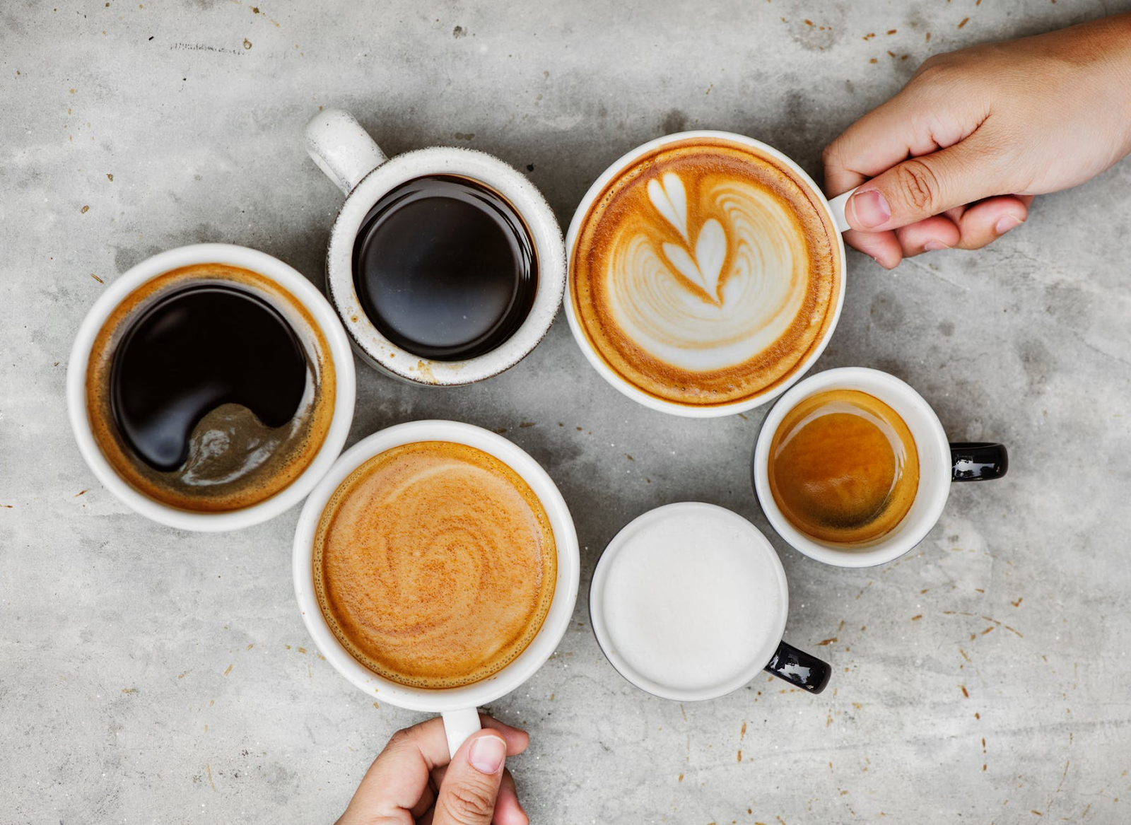 various mugs of coffee, some with latte art