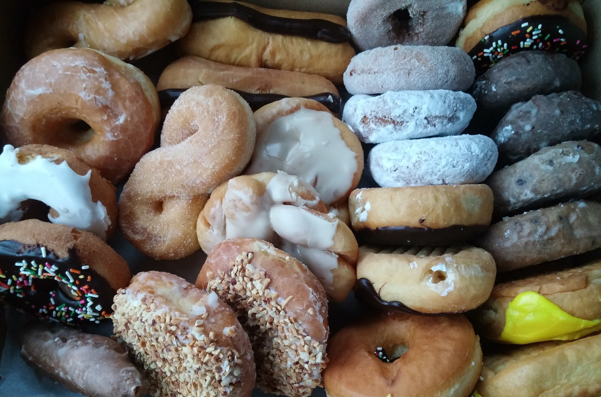 close up of various donuts and other pastries