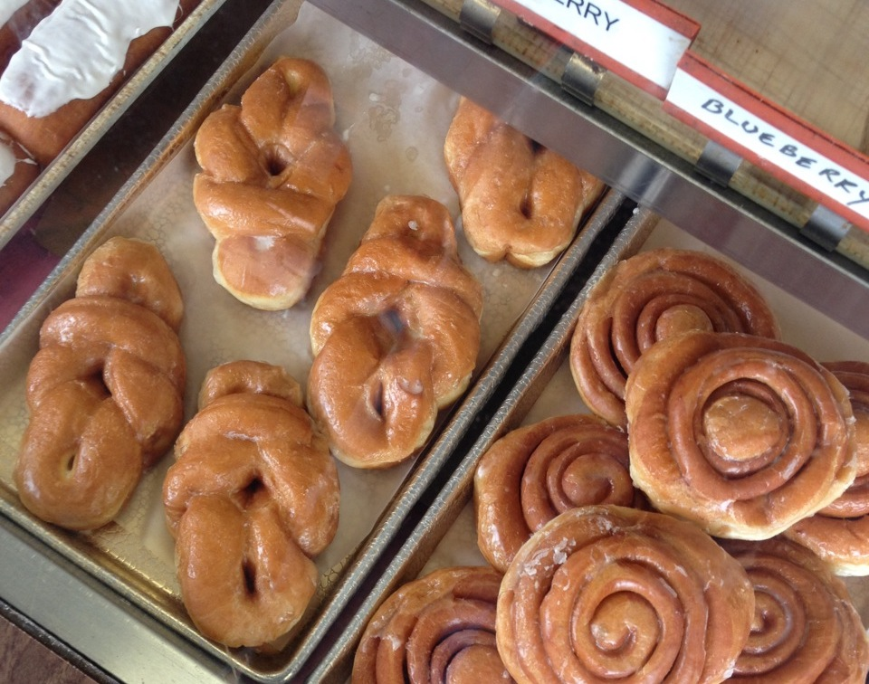 cinnamon rolls & other donuts behind glass at HoneyDip Donuts