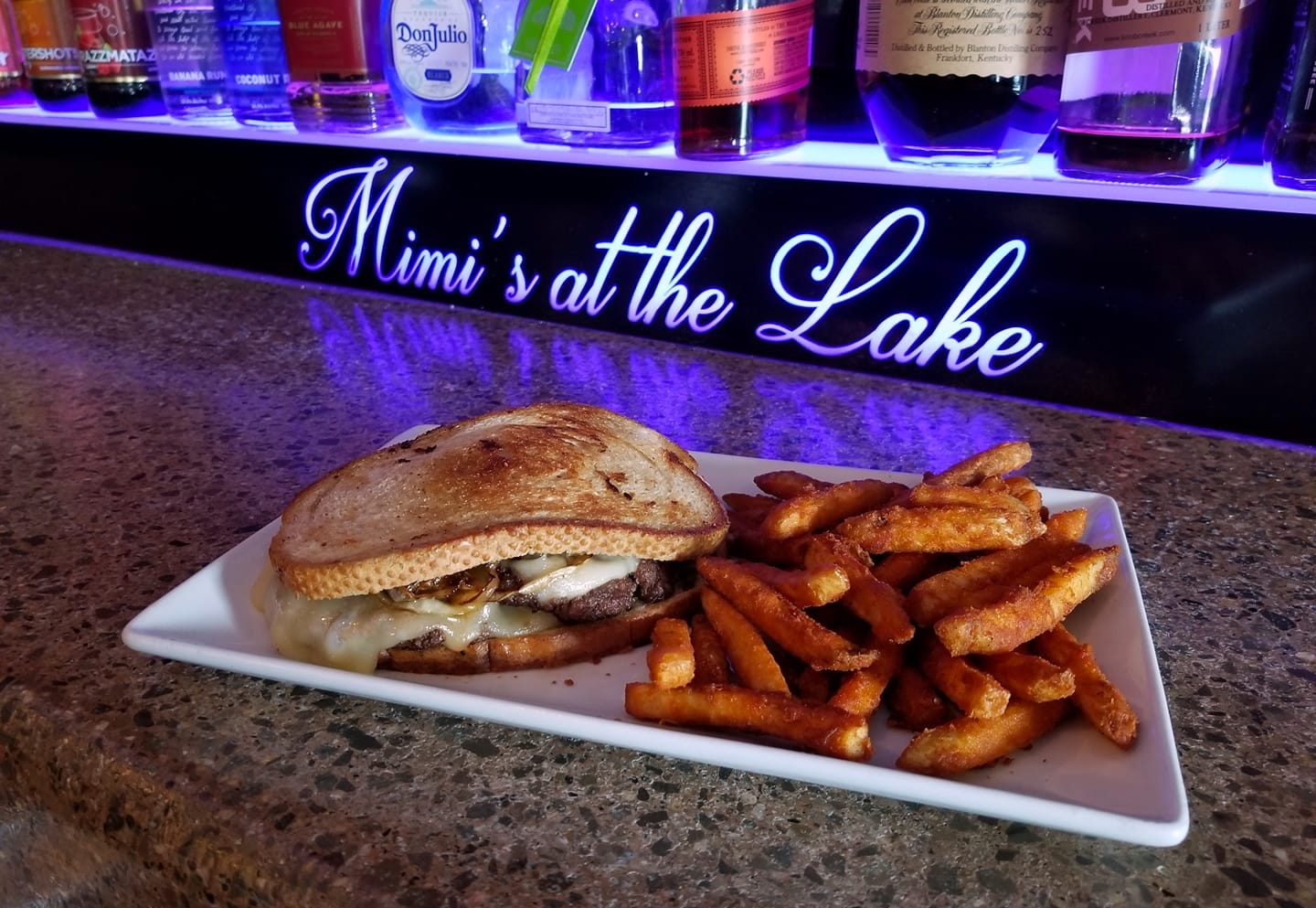 sandwhich & fries in front of lit Mimi's at the Lake sign