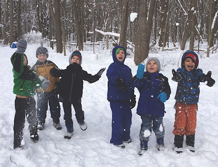 group of kids smiling & throwing snow in the air