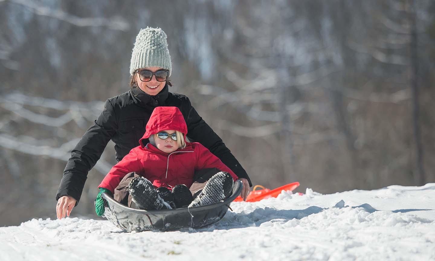 mother & child sledding in snow at Cleveland Metro Park