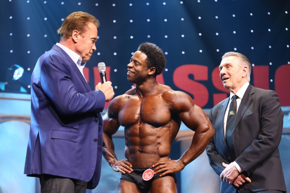 Arnold talking to bodybuilding contestant on stage of Arnold Classic