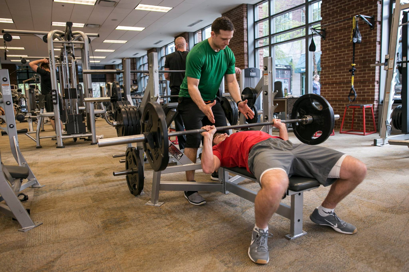 Man bench pressing with spotter at Arena Athletics,