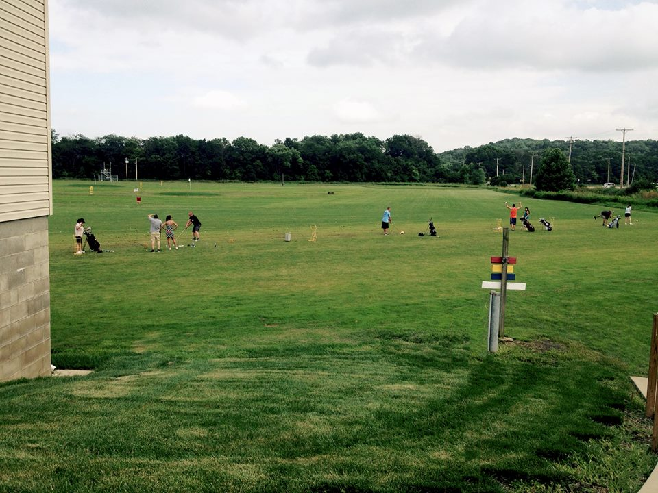 Driving range with various golfers