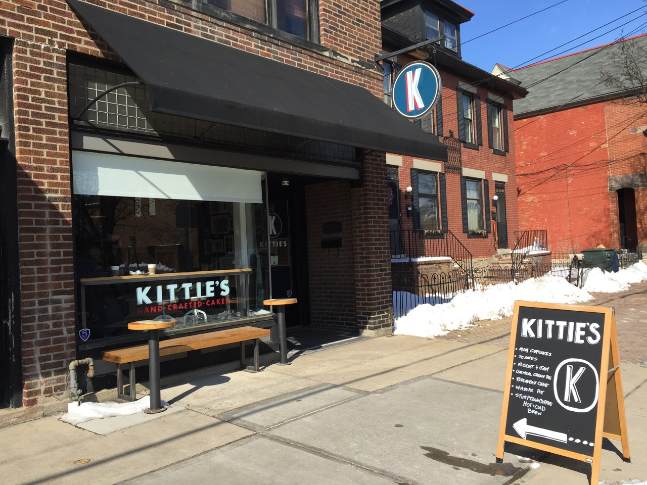front of Kittie's Cakes building with wooden bench outside