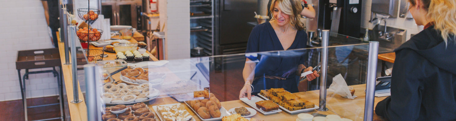 woman looking at pastries behind glass