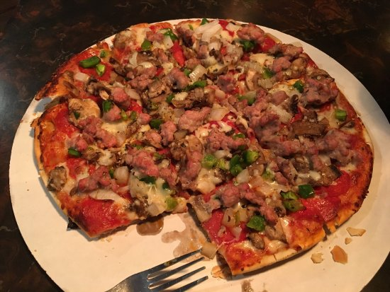pizza with sausage, green pepper, and other toppings