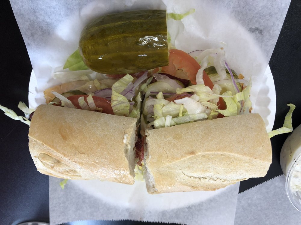 A sandwich with a pickle on the side from Richie's New York Corner Deli