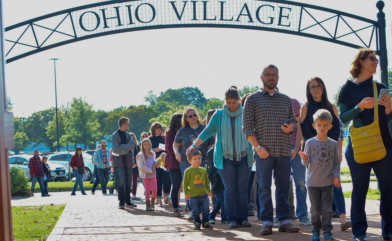 "People waiting in a line under a sign that reads ""Ohio Village"""