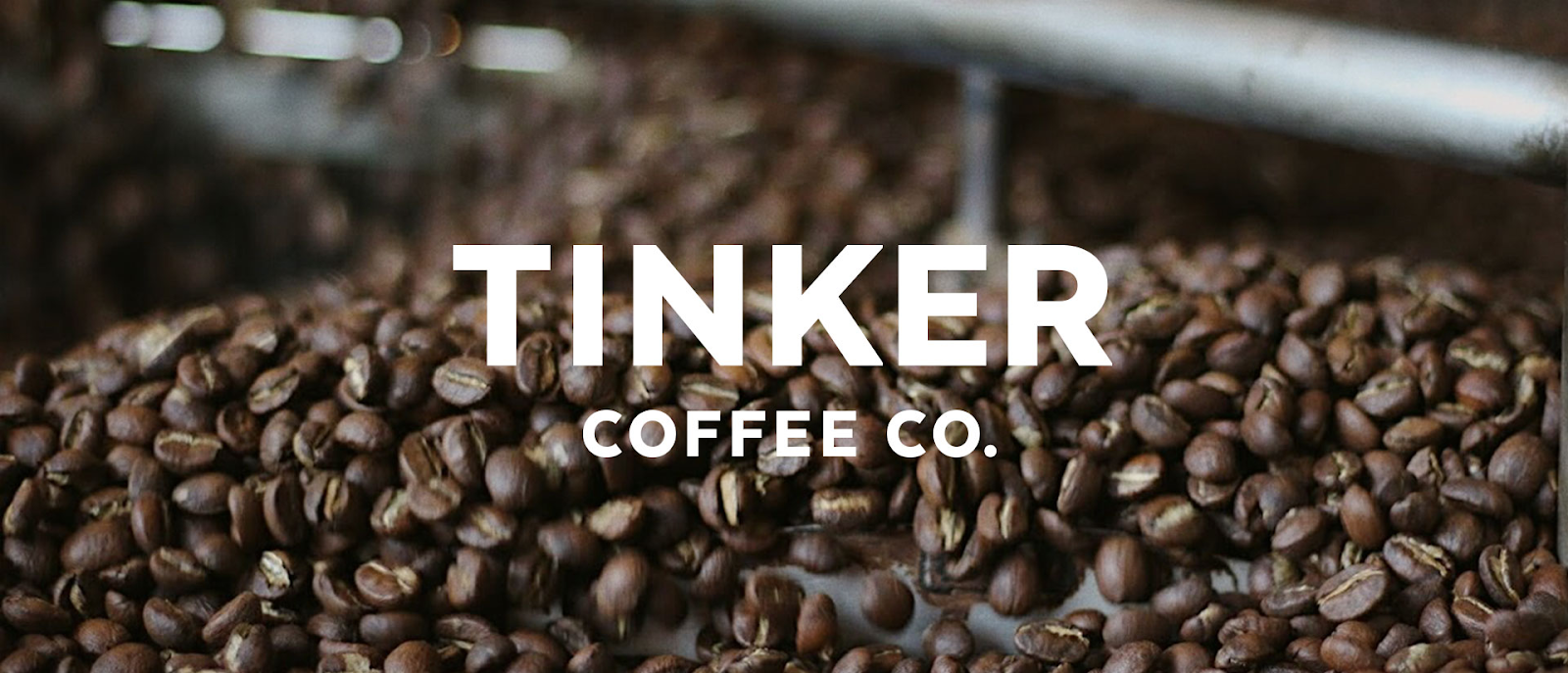 "Coffee beans from Tinker, with ""Tinker Coffee Co."" overlaid on the image in white text"