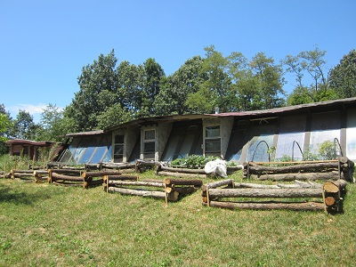 Short house with large windows with enclosures in front lawn made of logs