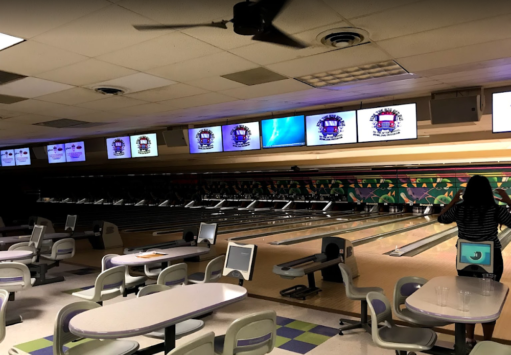 Tables and chairs in front of bowling lanes and brightly lit display screens