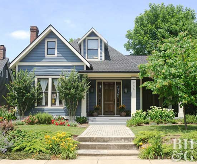 Blue two-story home with white trim and black and brown accents, lush greenery in front yard