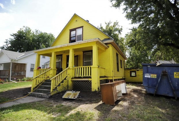 Dirty yellow two-story home with trash and dumpster