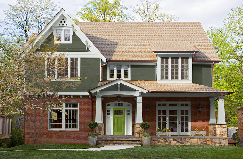 Red brick and green clapboard three-story home with white trim and accents