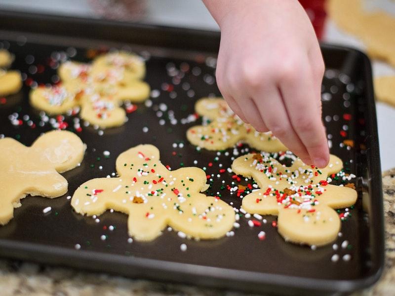 putting sprinkles on gingerbread men sugar cookies