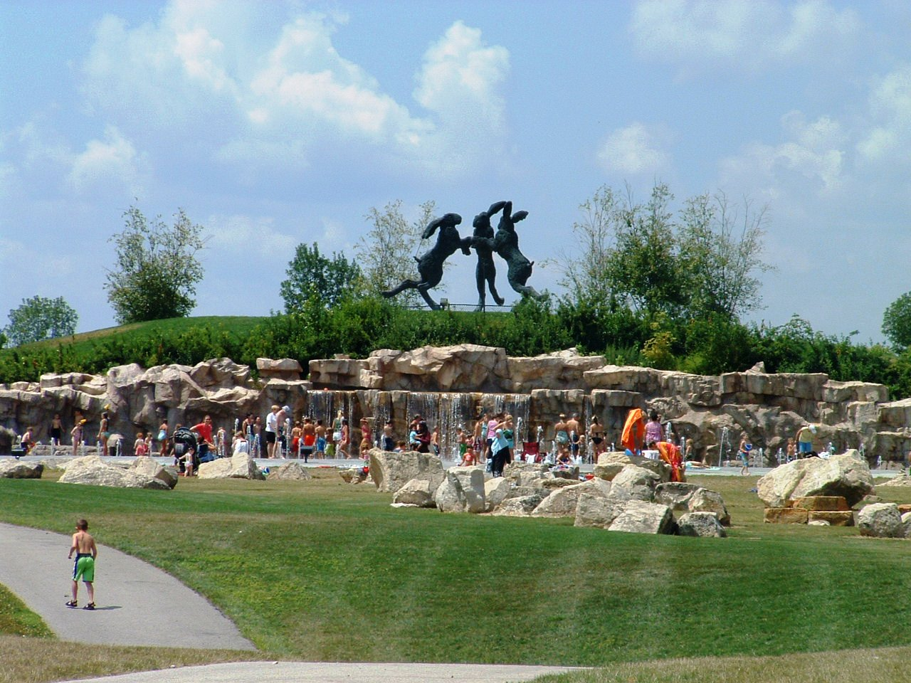 kids playing in a large water fountain in front of large statue of three dancing hairs