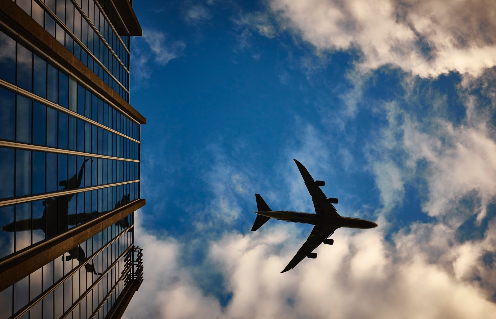 ground view of airplane flying over building