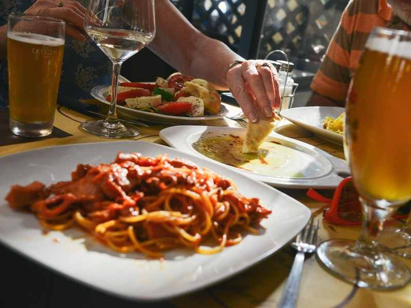 A table with Italian food, wine, and beer