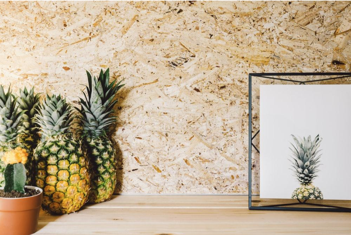 A holographof a pinball sits on a wood ledge next to a few pineapples and other textural elements.