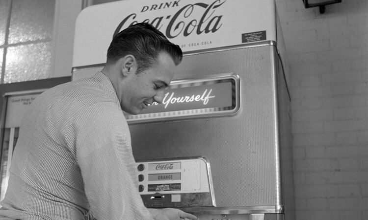 Vintage black and white photo of man at a Coca Cola vending machine