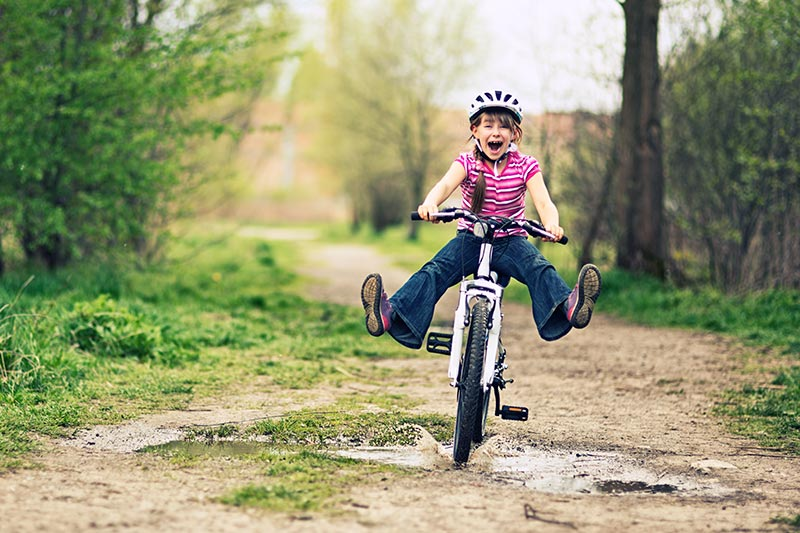 Girl riding her bike through a puddle
