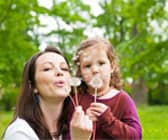 Mom and Daughter blowing dandelion seeds - balloon sinuplasty works