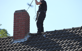 Worker Cleaning a Chimney