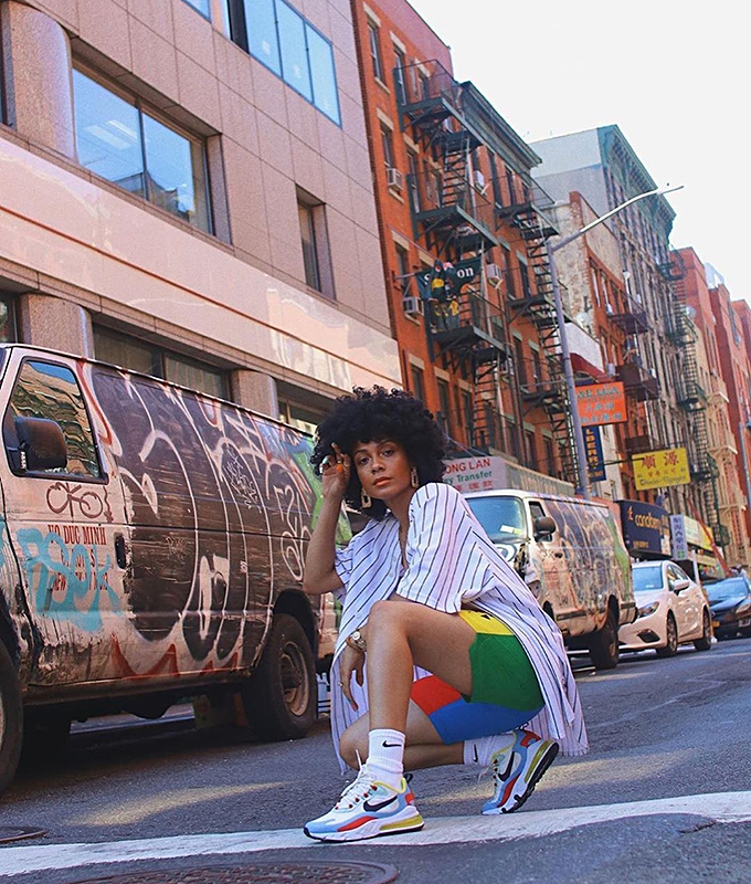 Cool young lady crouching down wearing sneakers in New York