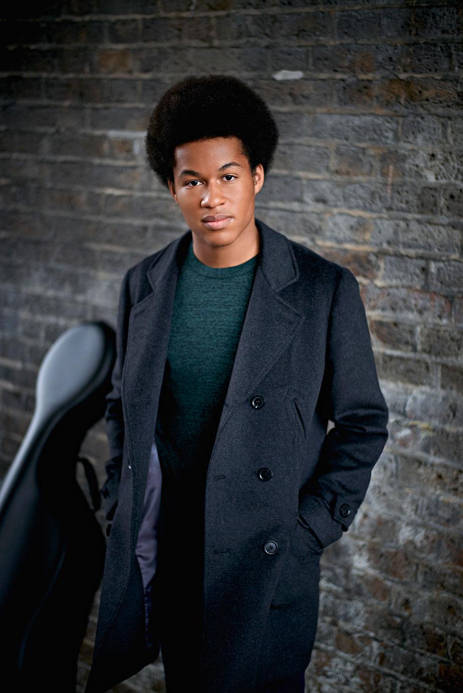 Cellist Sheku Kanneh-Maso editorial shoot against grey brick wall