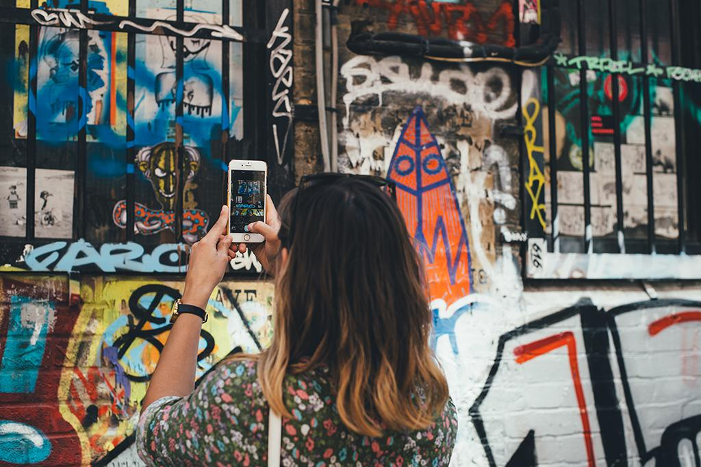 woman using iphone to instagram graffiti