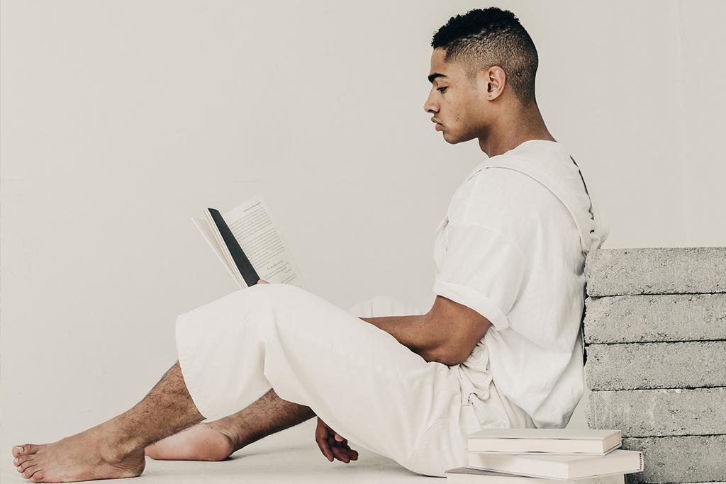 man reading books in empty room