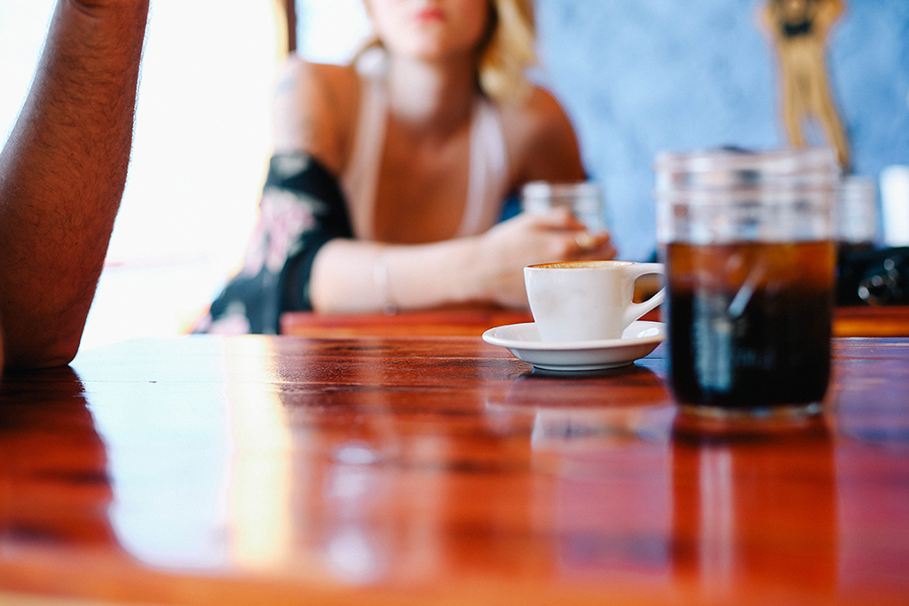 table with tea cup, glass of coke and people