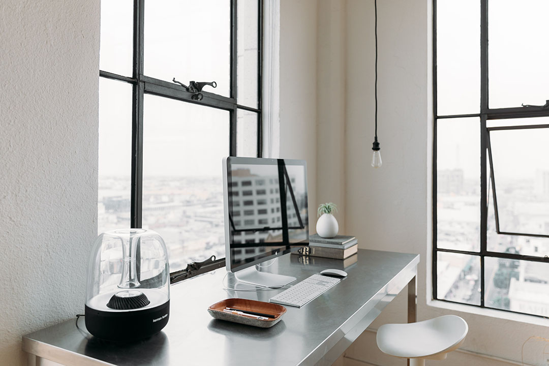 iMac on a desk with a lamp next to windows