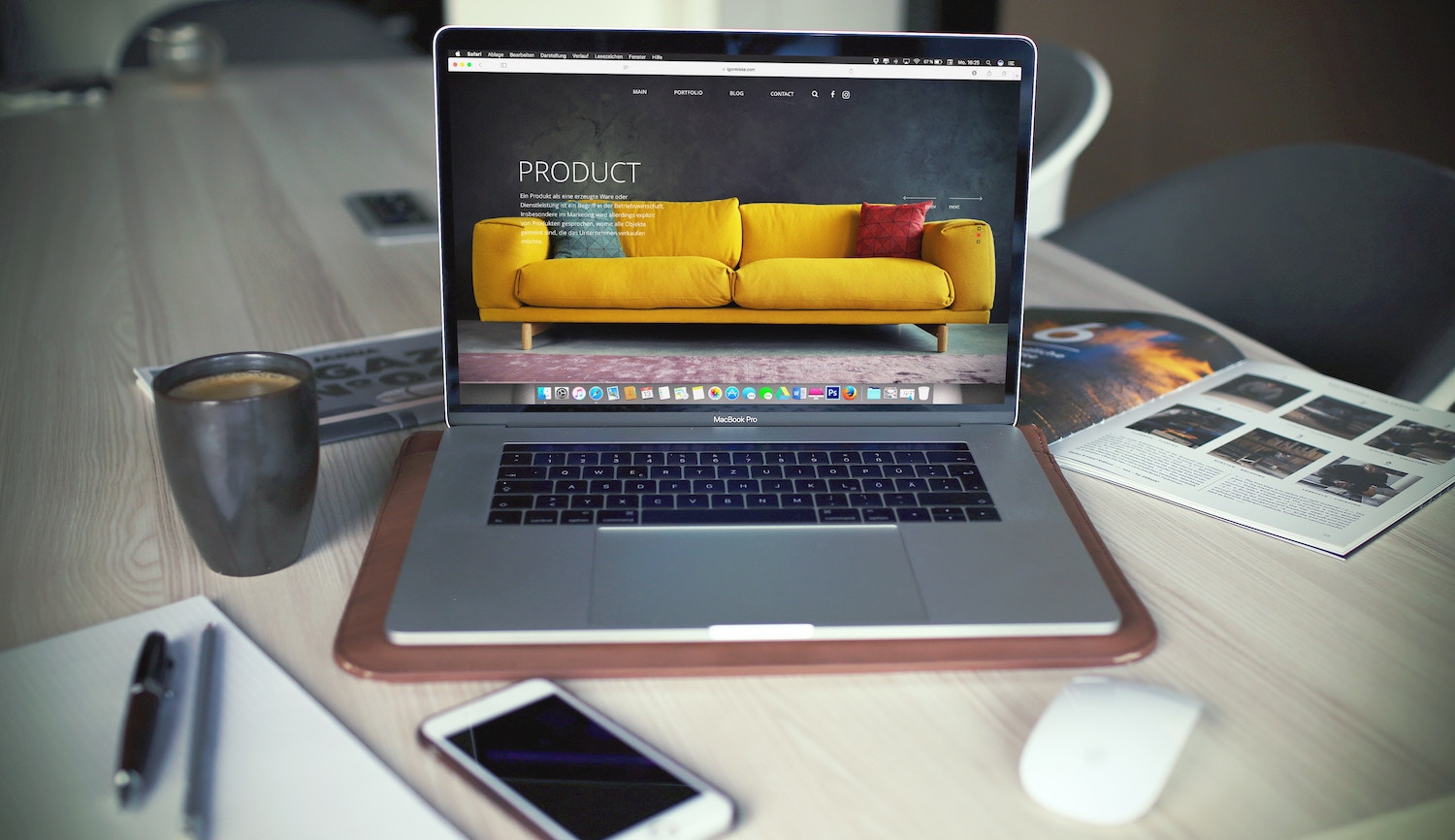 macbook on desk with mug of coffee smartphone notebook pen mouse and magazine