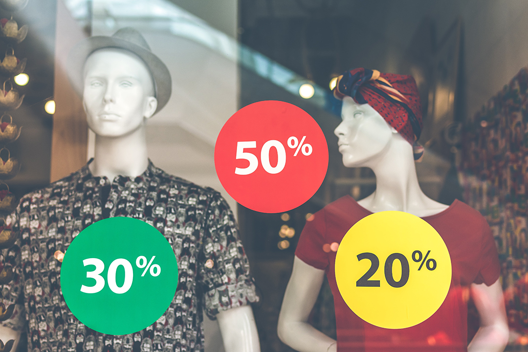 Mannequins in a shop with window stickers displaying sale discounts