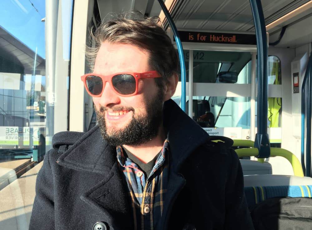David Parry wearing sunglasses and smiling on a bus