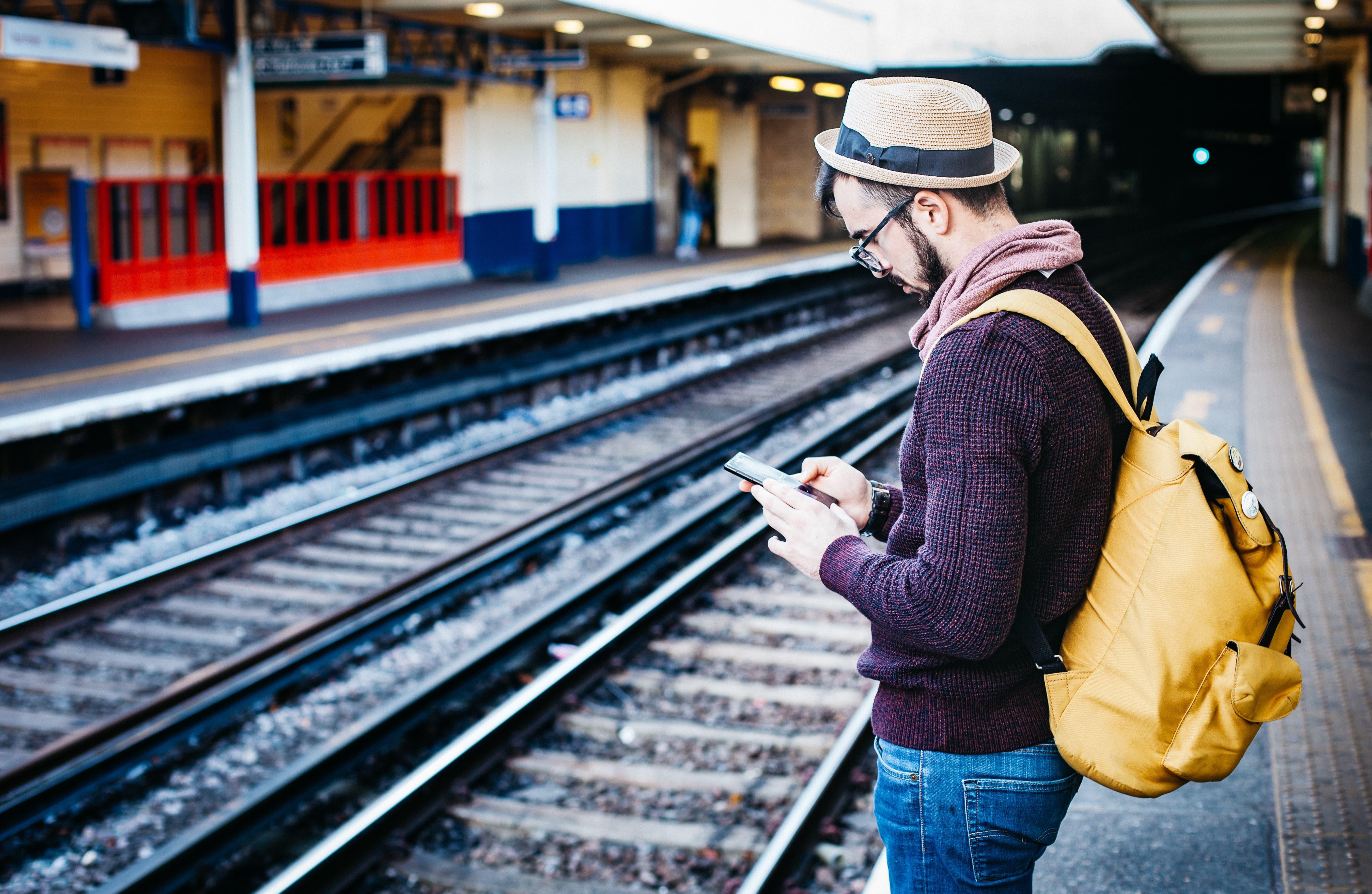 Man using an app at train station