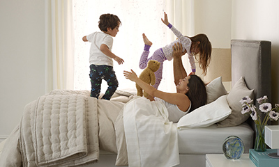 A woman plays with her children on the bed